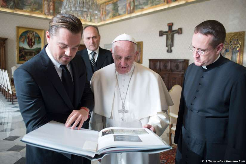 Actor Leonardo DiCaprio and Pope Francis look at a book during their meeting in the Apostolic Palace at the Vatican Jan. 28.