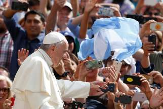 An item with the national colors of Argentina is thrown at Pope Francis as he greets the crowd during his general audience in St. Peter's Square at the Vatican June 13. The pope caught three objects of clothing or flags thrown at him within a span of a few seconds.