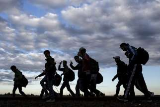 Migrants walk along rail tracks as they arrive to a collection point in the village of Roszke in Hungary after crossing the border from Serbia Sept. 6.