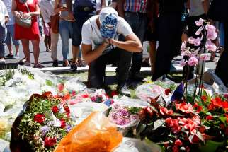 A man prays in front of a makeshift memorial July 15 in Nice, France, as people pay tribute near the scene where a truck ran into a crowd killing more than 80 people the previous evening.