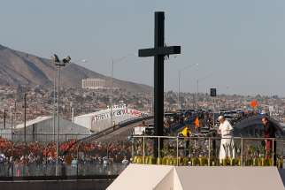 Pope Francis prays at a cross on the border with El Paso, Texas, before celebrating Mass at the fairgrounds in Ciudad Juarez, Mexico, Feb. 17.