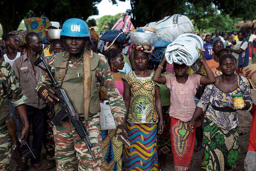 A U.N. peacekeeping soldier guards women fleeing Zike, Central African Republic, as they arrive April 26 in the village of Bambara.