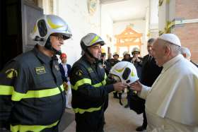 A firefighter hands Pope Francis a fire helmet made specifically for him to wear June 16, 2019, as he visits the Camerino cathedral, which suffered major damage during an earthquake in October 2016.