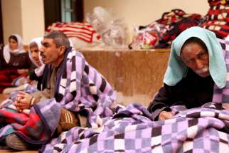 Displaced people from the minority Yezidi community keep warm under blankets as they take refuge in a building in Shikhan, Iraq, Jan. 19. Thousands of Iraq's religious minorities were displaced by vicious attacks by Islamic State militants last summer.