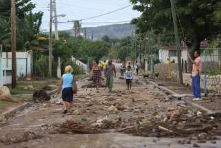 People walk on the street after strong waves hit the coast Oct. 4 near Santiago de Cuba ahead of the arrival of Hurricane Matthew.