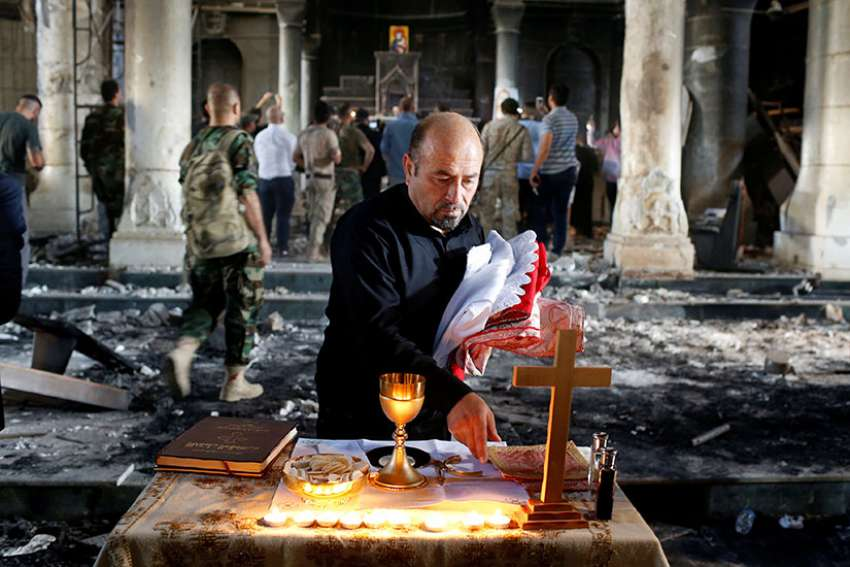 An Iraqi man prepares a makeshift altar for the first Sunday Mass Oct. 30, 2016 at the Church of the Immaculate Conception in Qaraqosh after it was recaptured from Islamic State militants.