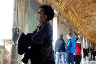 A visitor wears a mask for protection from the coronavirus while touring the Vatican Museums Feb. 2, 2020. The Vatican has announced that museums and necropolis tours will be closed to the public from Nov. 5-Dec. 3 as Italy faces increased COVID-19 cases and restrictions.