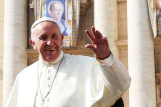 Pope Francis waves as he leaves his general audience in St. Peter's Square at the Vatican Oct. 18.