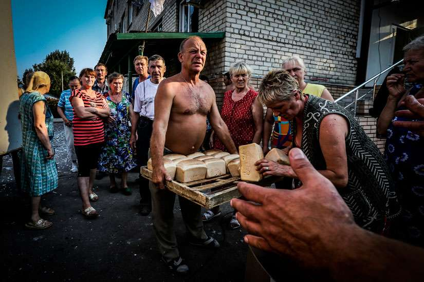 People living in shelters receive bread trays donated by members of the Donetsk People's Republic militias in Ilovaysk, Ukraine, in this Aug. 14, 2014 file photo,