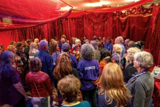 A singer leads the group in a musical prayer inside a red tent on the convention centre floor designated as the Women's Sacred Space.