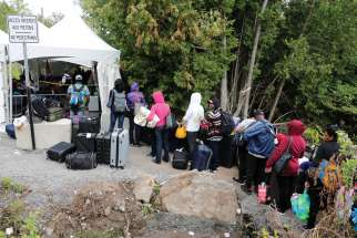 A group of Haitians wait to cross the U.S.-Canada border into Quebec from New York.