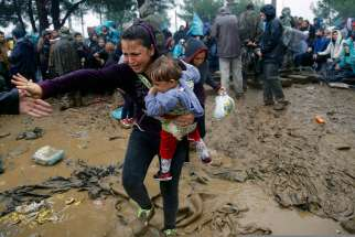 A Syrian refugee woman cries as she carries her baby through the mud to cross the border from Greece into Macedonia near the Greek village of Idomeni Sept. 10.