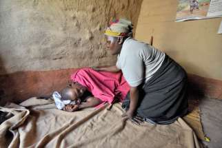 Home-based care worker Olipa Mkandawire prays for a man living with AIDS in Matuli, Malawi, in this 2009 photo. Marking World AIDS Day Dec. 1, African bishops commended families and parishioners caring for people with HIV as the Year of Mercy approaches.