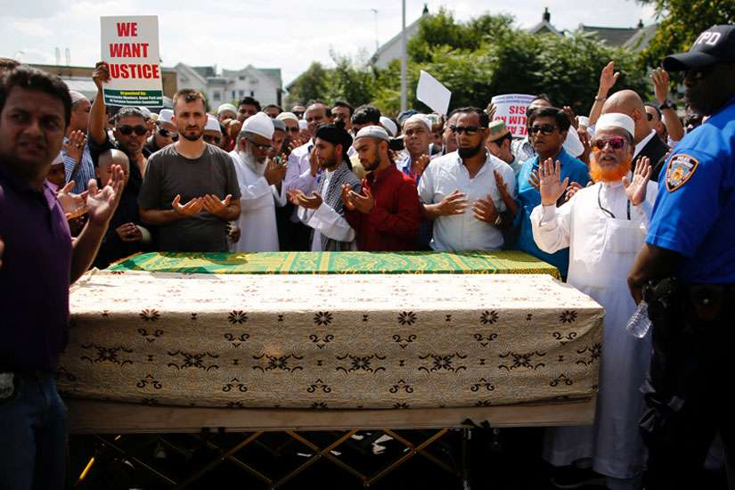 A crowd of community members pray next to the coffins as they gather for the funeral service of Imam Maulama Akonjee in the Queens borough of New York City, on August 15, 2016.