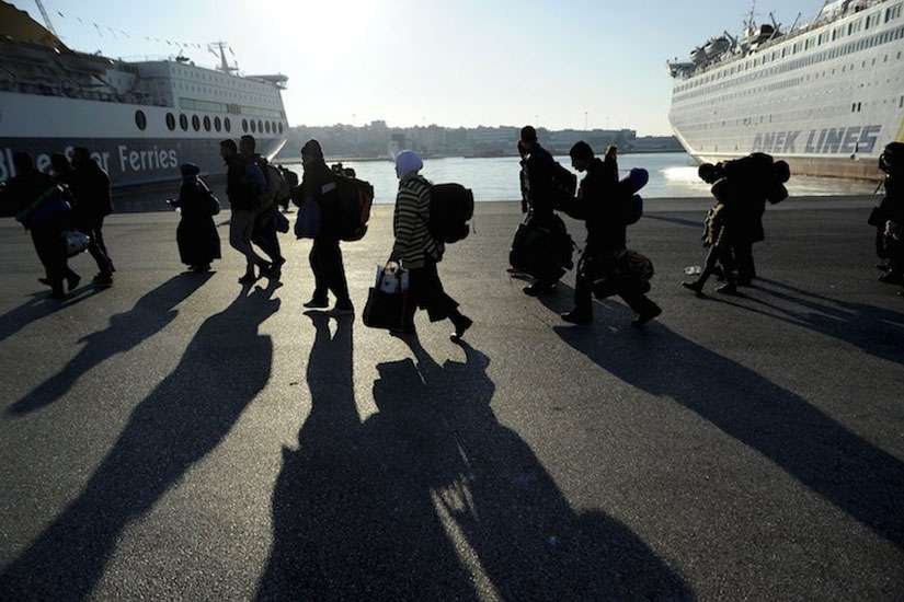 Refugees and migrants walk after disembarking from the passenger ferry Eleftherios Venizelos from the island of Lesbos at the port of Piraeus, near Athens, Greece, Dec 26, 2015.