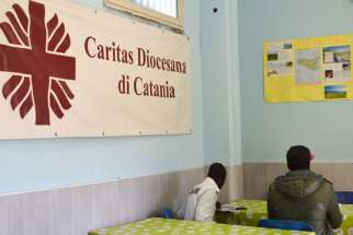Migrants sit at the Caritas center in Catania, Sicily. The Indian branch of the Catholic social welfare organization, Caritas, has announced plans to fight discrimination and recruit transgender people.