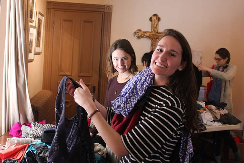 Katie Moretta, left, and Isabel Cumming look through piles of donated clothing during the annual St. Gianna clothing exchange.