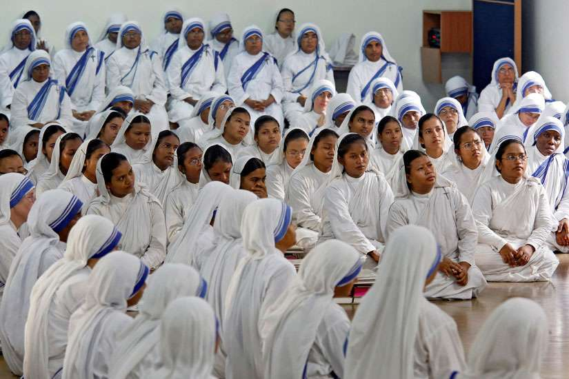 Members of the Missionaries of Charity pray Aug. 26 near the tomb of Blessed Teresa of Calcutta in celebration of her 106th birthday in India. Mother Teresa, founder of the Missionaries of Charity, will be canonized at the Vatican Sept. 4.