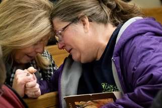 Judy Hawkins and Theresa Winkler embrace before a Mass for Jamie Schmidt Nov. 20 at St. Anthony of Padua Church in High Ridge, Mo. Schmidt died Nov. 19 after being shot while shopping earlier that day at the Catholic Supply store in west St. Louis County.