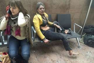 Injured people are seen at the scene of explosions at Zaventem airport near Brussels March 22.