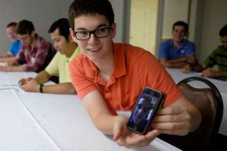 A Nashville seminarian holds a cellphone Aug. 12 showing a video chat to a fellow seminarian in Rome. A former BBC executive will help reform the Vatican's media services after being appointed to the media committee.