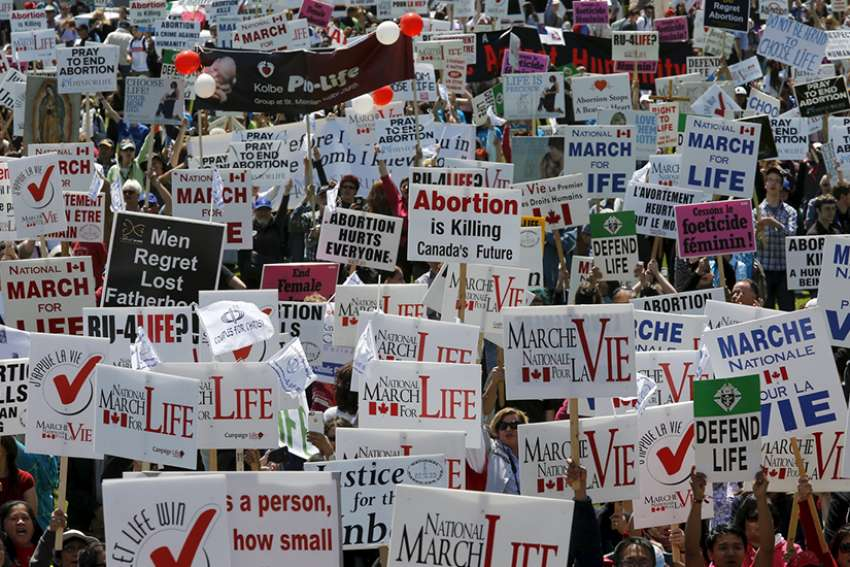 Demonstrators hold signs during a May 14 pro-life protest on Parliament Hill in Ottawa, Ontario in 2015.