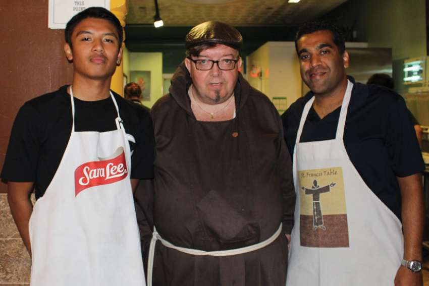Br. John Frampton is flanked by volunteers Sonny Doria (left) and Lionel Alleluia at St. Francis Table.