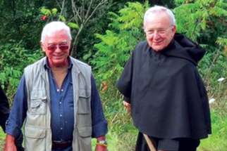 Ted Harasti, left, and Br. Paul Koscielniak break ground on the rosary path.