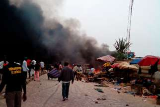 Smoke rises after a bomb blast at the market district in Jos, Nigeria, May 20. Back-to-back bombings killed at least 118 people and wounded 45 in the crowded business district of the central Nigerian city, the National Emergency Management Agency reporte d, in an attack that appeared to bear the hallmarks of Boko Haram insurgents.