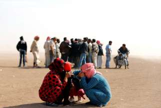 "Syrian refugees wait at the Turkish border near Sanliurfa, Sept. 24. Some Syrian refugees in Jordan say they welcome the military intervention to diminish Islamic State power, while others blame Syrian President Bashar Assad for turning a ""blind eye"" to infiltration by foreign militants."