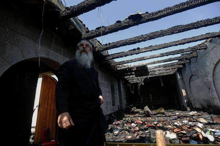 A clergyman stands inside the Church of Loaves and Fishes following a 2015 fire in Tabgha, Israel. Twenty months after having suffered serious damage from an arson attack, the atrium of the Benedictine church was reopened.