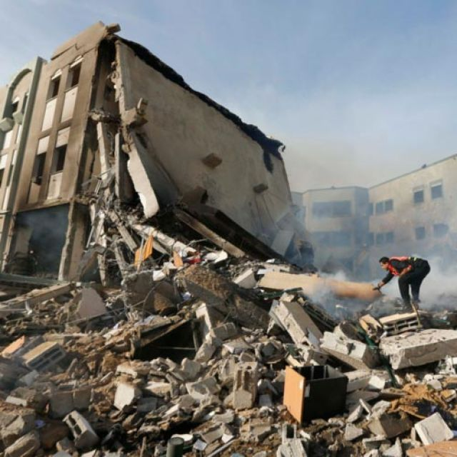 Palestinian firefighters extinguish a smoldering fire after an Israeli airstrike on the building of Hamas' Ministry of Interior in Gaza City Nov. 16. Catholic officials said Israeli and Palestinian leaders must make tough decisions to end the recent violence.