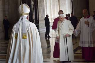 "Retired Pope Benedict XVI prepares to greet Pope Francis during the opening of the Holy Door of St. Peter's Basilica at the Vatican in this Dec. 8, 2015, file photo. In a written interview, the retired pope commented on the theme of mercy. ""Mercy is what moves us toward God, while justice makes us tremble in his sight, Pope Benedict said."