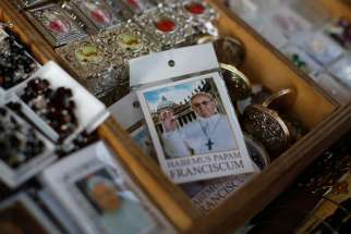 A rosary package with the image of Pope Francis is displayed in a tourist shop outside the Vatican in Rome.