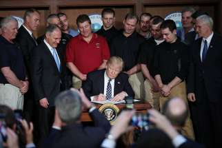 "U.S. President Donald Trump signs an executive order titled ""Energy Independence"" during a March 28 event at the Environmental Protection Agency headquarters in Washington. The order eliminates Obama-era climate change regulations and calls for a review of President Barack Obama's Clean Power Plan."