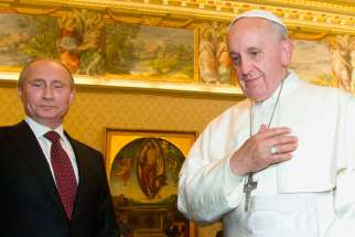 Pope Francis smiles alongside Russian President Vladimir Putin during a private audience at the Vatican Nov. 25, 2013.