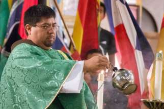 Father Urbano Vazquez swings a thurible over the altar at a Mass at the Shrine of the Sacred Heart in Washington.