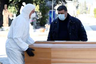 Men in Bergamo, Italy, transport a coffin of a person who died from the coronavirus disease in this photo shot March 16, 2020. A number of priests and religious women have been among the nearly 2,000 people who have died in Italy because of illness connected with COVID-19.