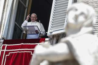 Pope Francis waves as he leads the Angelus from the window of his studio overlooking St. Peter's Square July 15 at the Vatican.