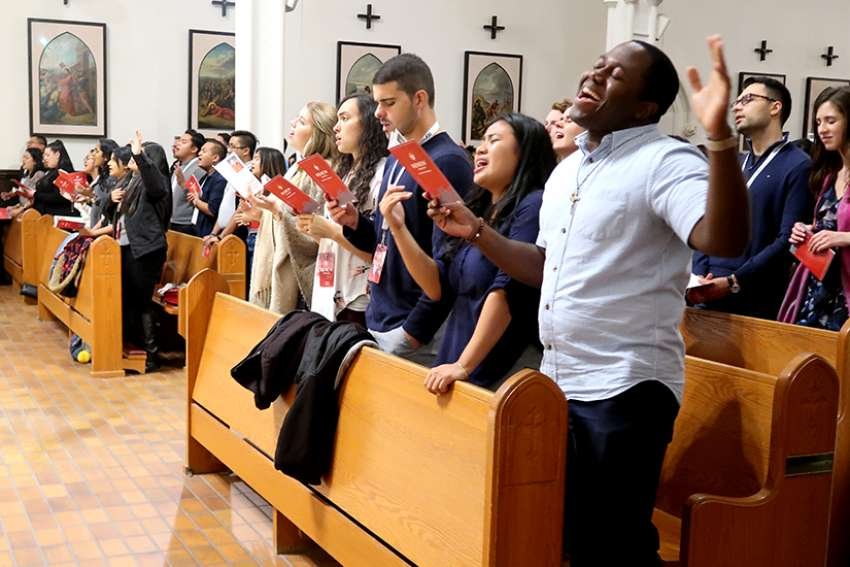 Renew Toronto participants sing during praise and worship before Holy Adoration at St. Basil's Parish at University of St. Michael's College.
