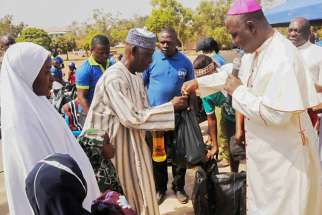 Archbishop Ignatius Kaigama presents relief material to internally displaced persons in Jos, Nigeria, Jan. 20. Many now flee to neighboring Cameroon to escape Boko Haram attacks.