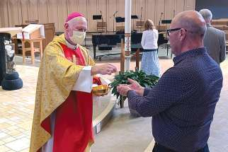 Bishop Mark Hagemoen distributes communion at the end of Mass May 24 at the Cathedral of the Holy Family in Saskatoon, the first weekend of phasing-in the resumption of public celebration of Mass in the diocese.