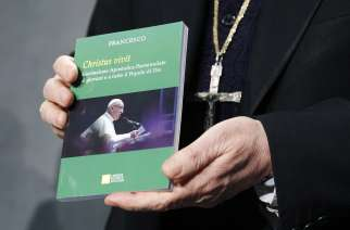"Cardinal Lorenzo Baldisseri, secretary-general of the Synod of Bishops, holds Pope Francis' apostolic exhortation, ""Christus Vivit"" (Christ Lives), during a news conference at the Vatican April 2. The document contains the Pope's reflections on the 2018 Synod of Bishops on young people, the faith and vocational discernment. Cardinal Lorenzo Baldisseri, secretary-general of the Synod of Bishops, holds Pope Francis' apostolic exhortation, ""Christus Vivit"" (Christ Lives), during a news conference for its presentation at the Vatican April 2, 2019."