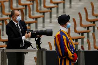 A Swiss Guard is seen as Vatican photographer Simone Risoluti works during Pope Francis' general audience in Paul VI hall at the Vatican Oct. 7, 2020. The weekend of Oct. 10-11, four Swiss Guards were found to have COVID-19 and are symptomatic, the Vatican confirmed Oct. 12.