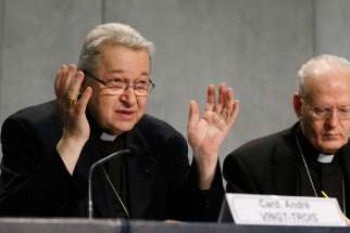 Cardinal Andre Vingt-Trois of Paris, one of three cardinals Pope Francis chose to serve as presidents of the extraordinary Synod of Bishops on the family, speaks during a press conference at the Vatican June 26. The press conference was held to unveil th e working document for the October extraordinary Synod of Bishops on the family. Also pictured is Hungarian Cardinal Peter Erdo of Esztergom-Budapest, synod relator.