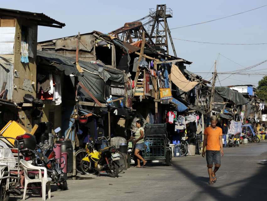 People walk past makeshift homes in early May at a shantytown outside Manila, Philippines.