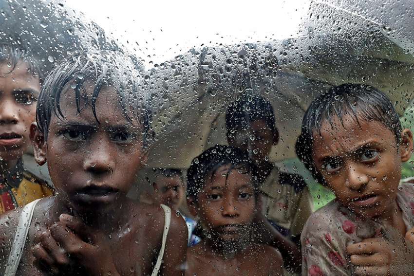 Rohingya refugee children are seen through a rain-covered window Sept. 19 at a camp in Cox's Bazar, Bangladesh.