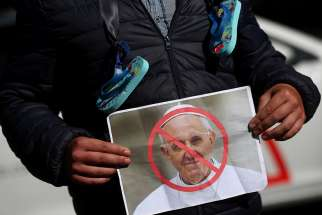 A protester holds a picture of Pope Francis during an Aug. 25 demonstration against clerical sex abuse in Dublin.