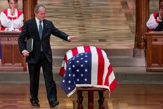 Former U.S. President George W. Bush touches the flag-draped casket of former President George H.W. Bush after speaking at his father's state funeral Dec. 5 at the Episcopal Church's Washington National Cathedral.