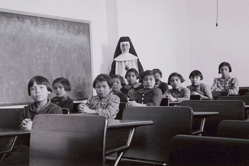 "In this 1940 photo, a group of female students and a nun pose in a classroom at Cross Lake Indian Residential School in Manitoba. Blair Stonechild, a professor of indigenous studies at First Nations University of Canada, says the residential school periods in Canada was ""spiritual abuse"" and has deep roots."